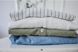 nachhaltige Mode bzw. Kleidung gestapelt auf einem weißen Stuhl