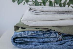 nachhaltige Mode bzw. Kleidung gestapelt auf einem weißen Stuhl mit Eukalyptuszweig